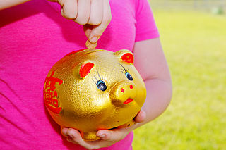 Girl Putting Money into Piggy Bank