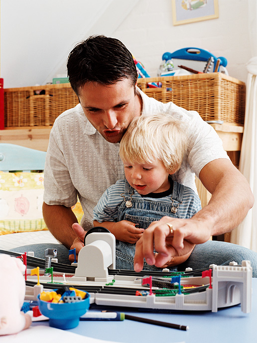 Adult playing cars with child