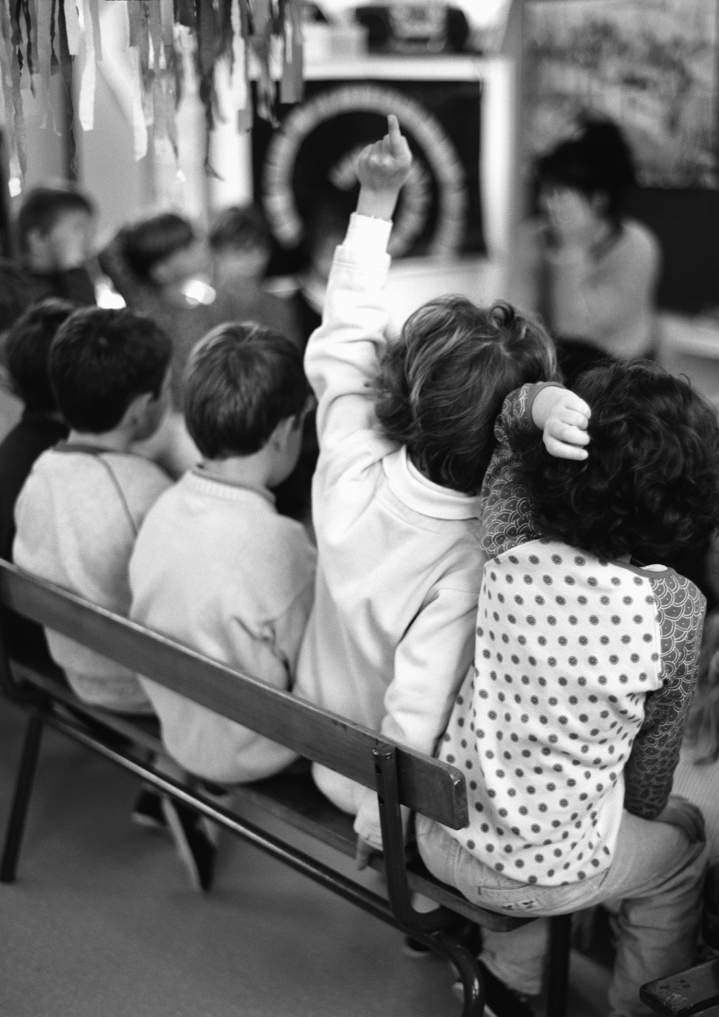child raising hand in class